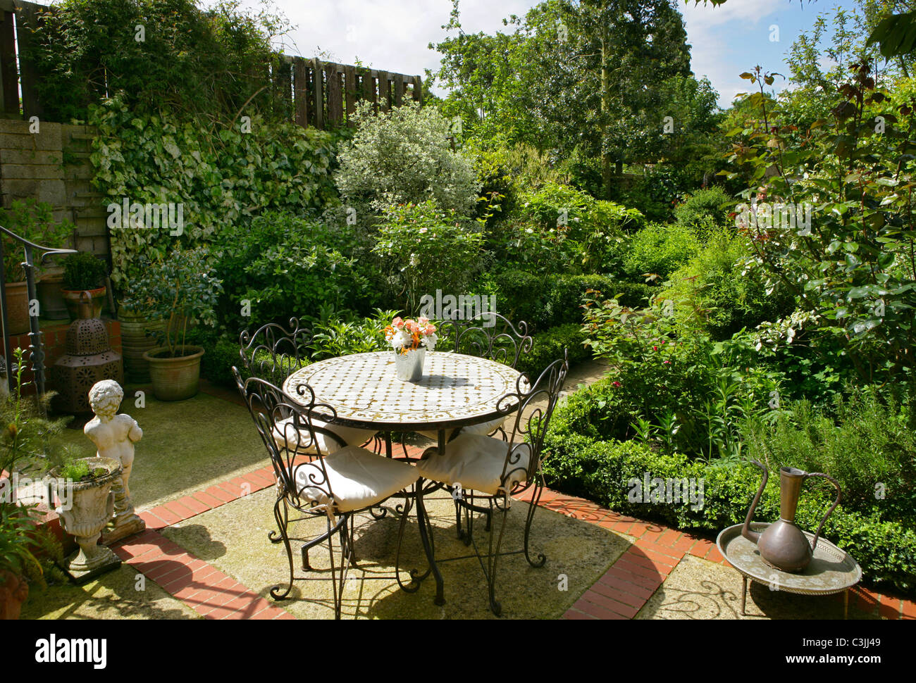 Small town garden patio with metal furniture and tiled for Small metal patio set