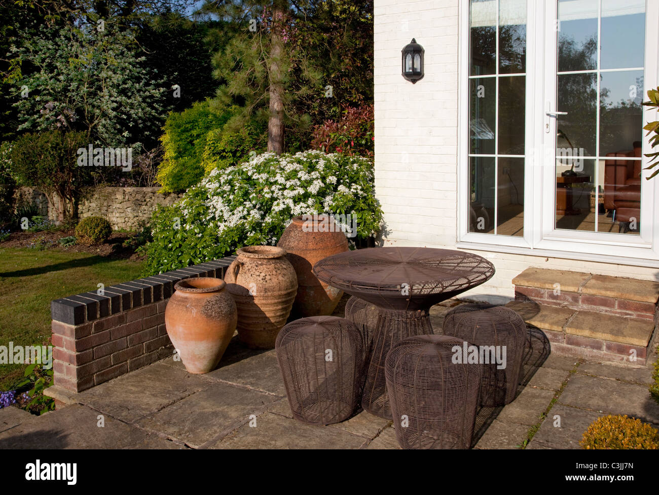 Stock Photo   Stone Patio In English Garden With Terracotta Pots And  Contemporary Metal Table And Chairs