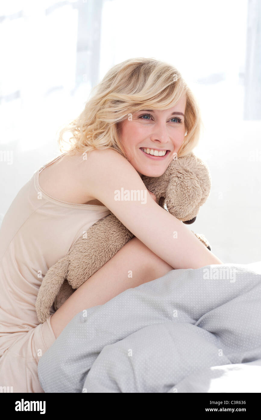 germany leipzig young woman sitting on bed smiling. Black Bedroom Furniture Sets. Home Design Ideas