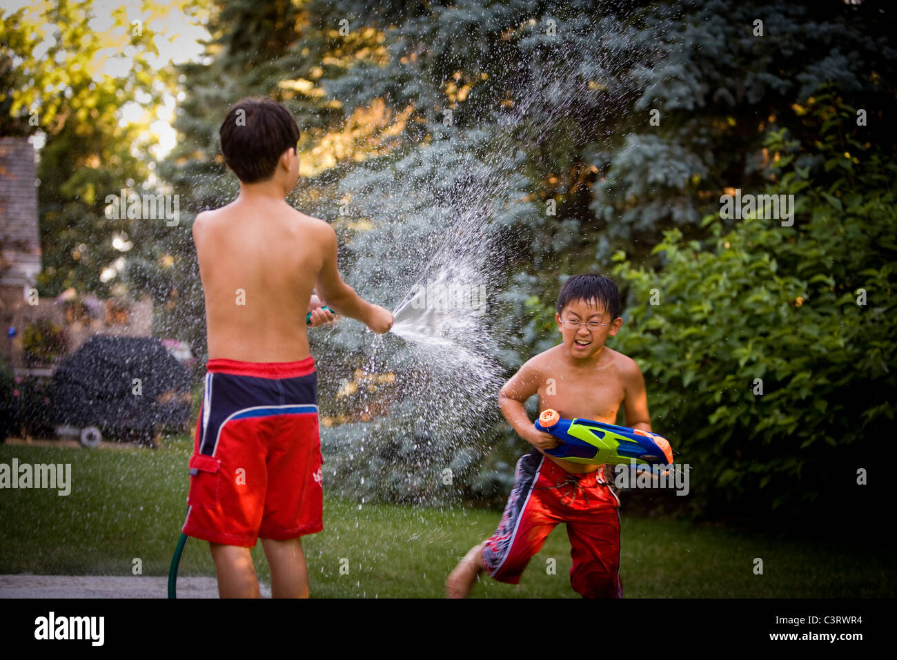 young boys having a water fight in the backyard stock photo
