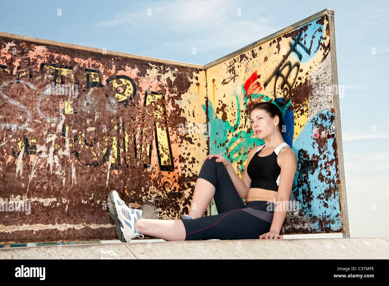 Graffiti wall training - Stock Photo Woman Resting After Training And Keeping Fit Sitting By A Graffiti Wall