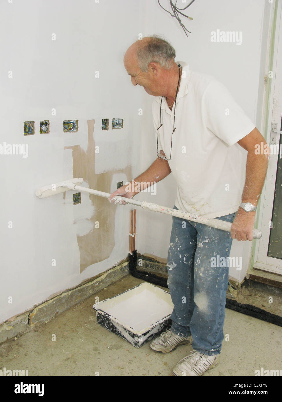 painting plaster wallspainter decorator painting newly plastered walls Stock Photo