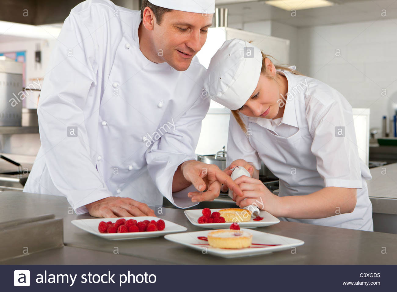 chef teaching trainee how to garnish gourmet dessert in commercial stock photo royalty free. Black Bedroom Furniture Sets. Home Design Ideas