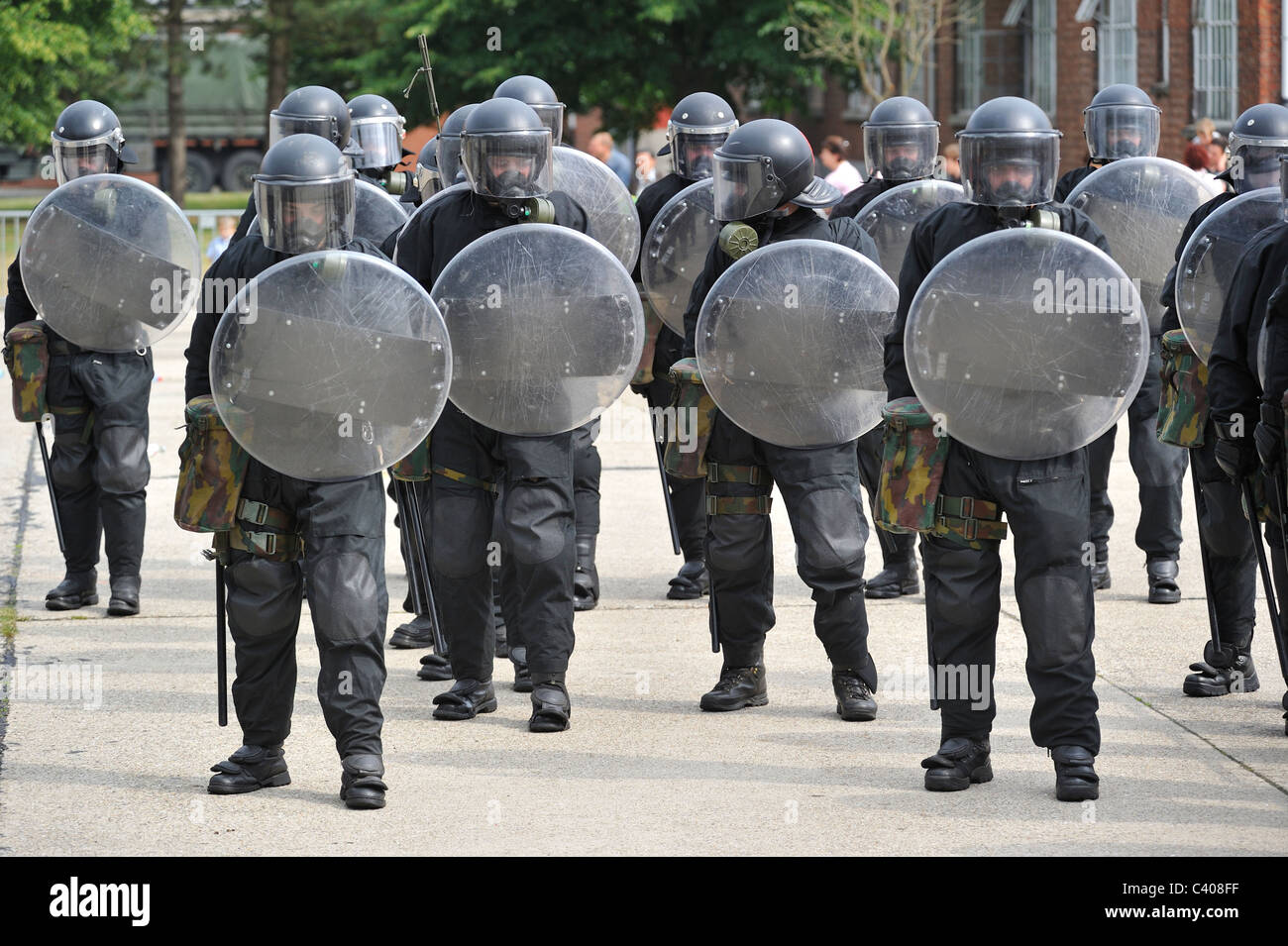 Riot squad police officers forming a protective barrier ...