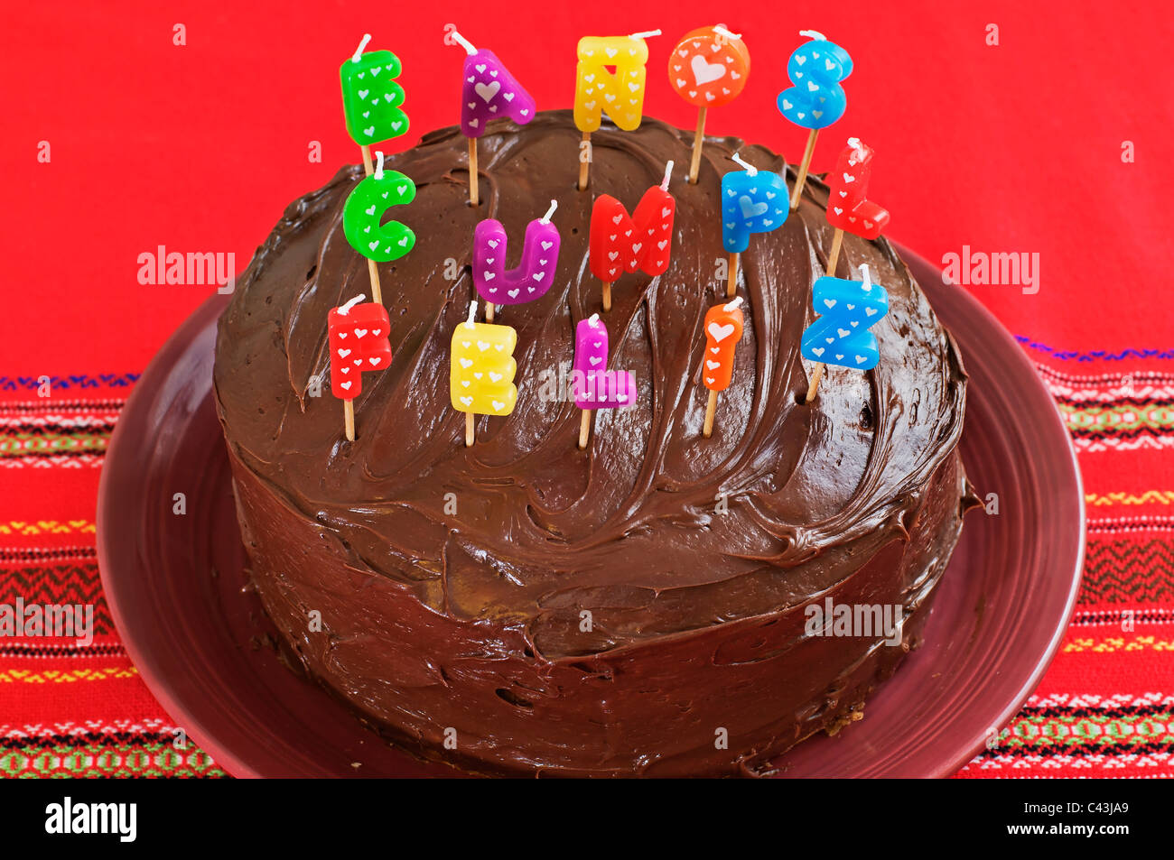 Layered birthday cake with chocolate frosting and decorated with ...