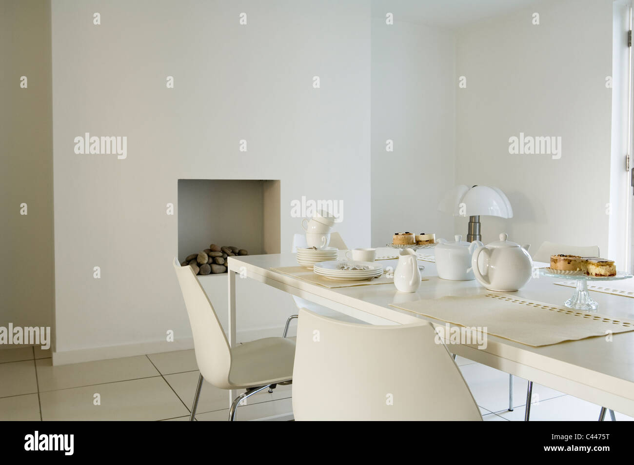 Minimal Modern Dining Area With White Table And Chairs Open Fireplace