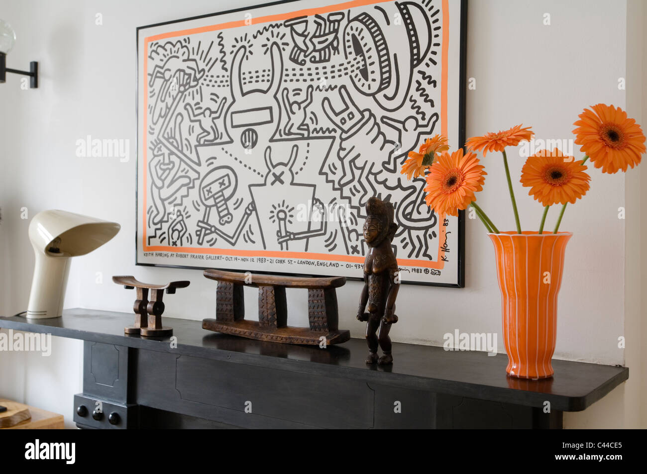 Smaller tsonga and larger zulu headrest on mantelpiece with keith smaller tsonga and larger zulu headrest on mantelpiece with keith haring artwork and orange vase with gerbera reviewsmspy