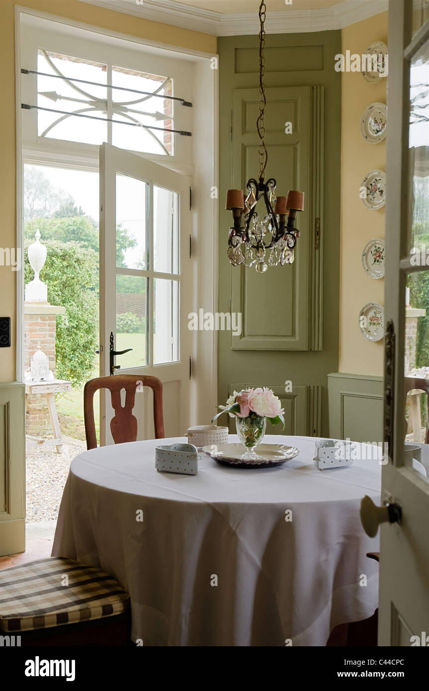 Dining table with tablecloth in country style kitchen with stock dining table with tablecloth in country style kitchen with chandelier decorative plates and view through back door to garden arubaitofo Image collections