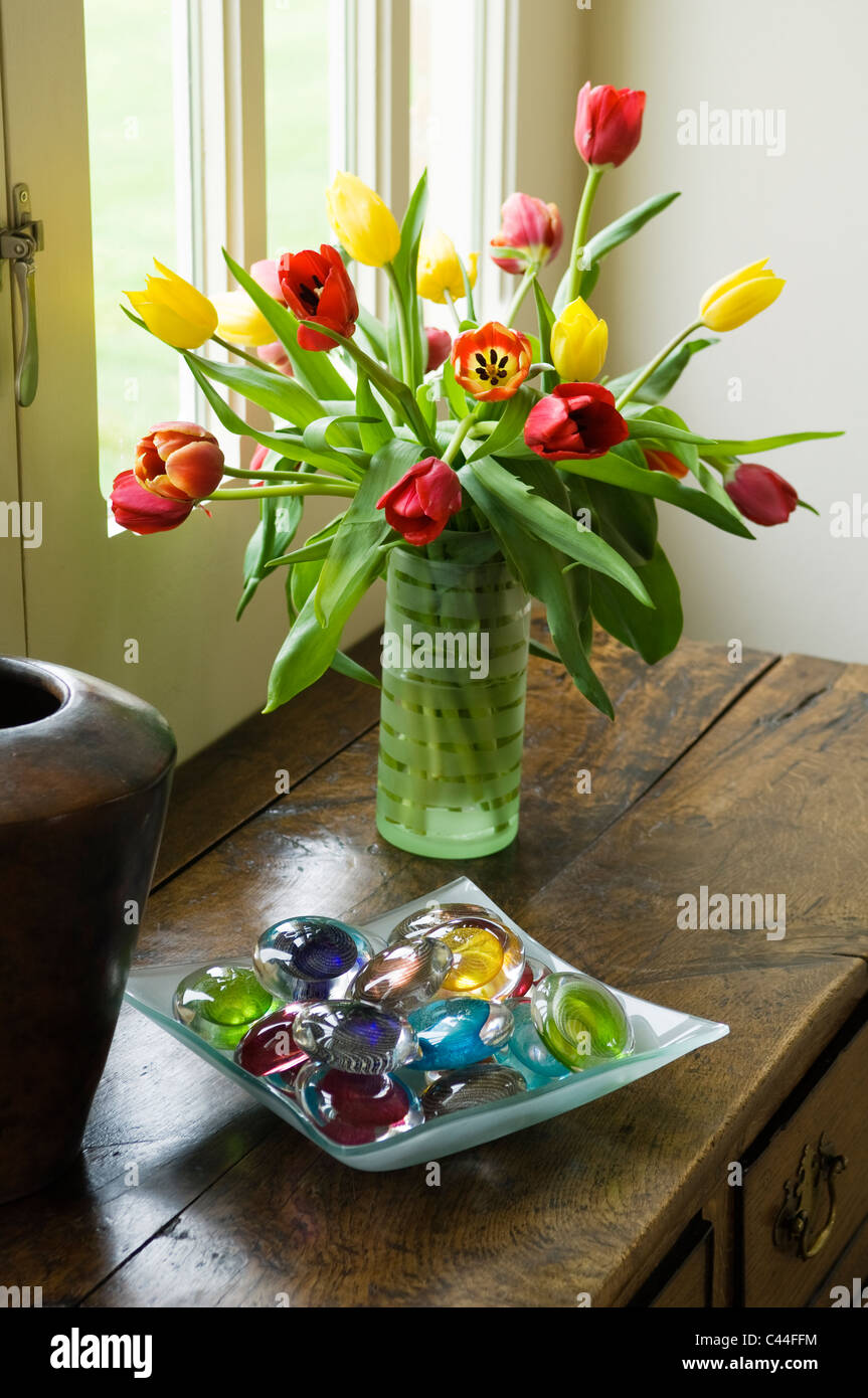 Vase of tulips on old wooden chest along with bowl of coloured vase of tulips on old wooden chest along with bowl of coloured glass pebbles reviewsmspy