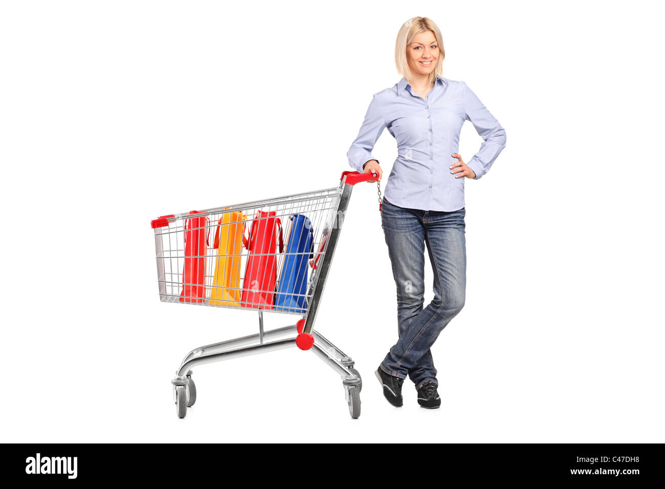 Smiling female posing next to a shopping cart full with shopping ...