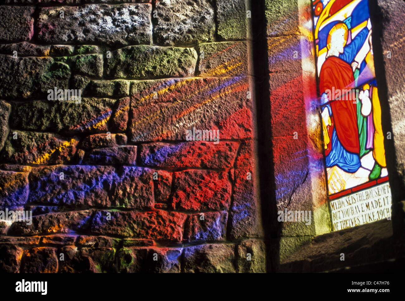 Bright Sunlight Refracted Through A Stained Glass Window Casts Colorful Patterns On The Plain Stone Wall Of An Old Church In Adare Ireland