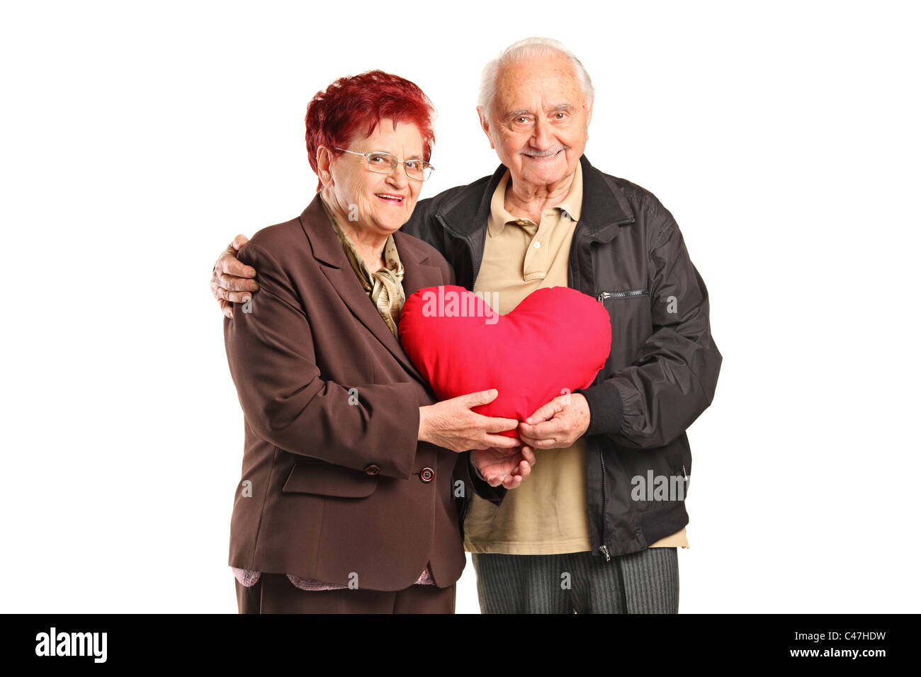 Man Shaped Pillow Senior Man And Woman Holding A Heart Shaped Pillow Stock Photo