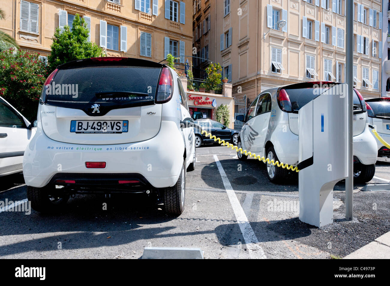 auto bleue electric cars at a charging point in the french. Black Bedroom Furniture Sets. Home Design Ideas