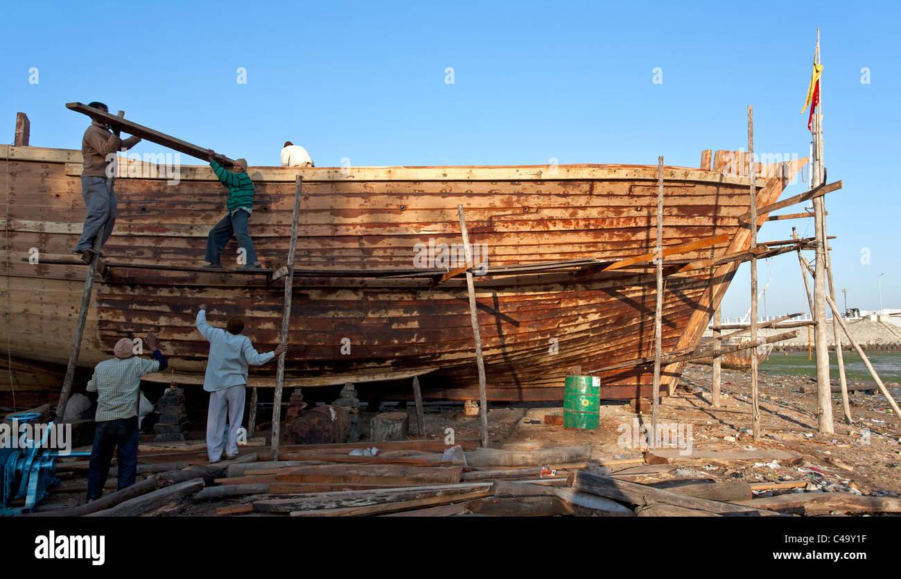 Men building a traditional fishing boat. Shipyard. Diu ...