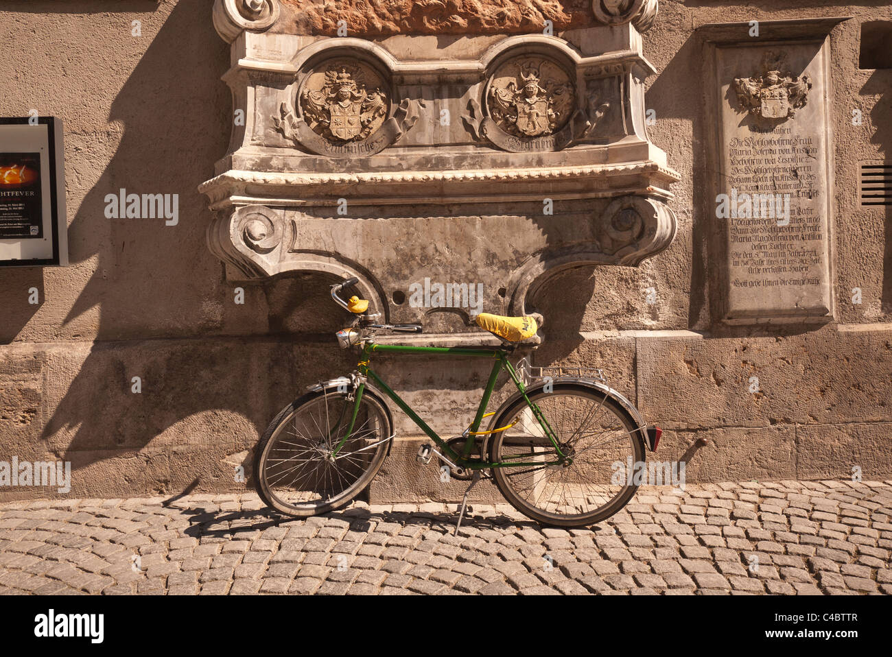 A green bicycle with a yellow seat and rubber ducky stands in front ...