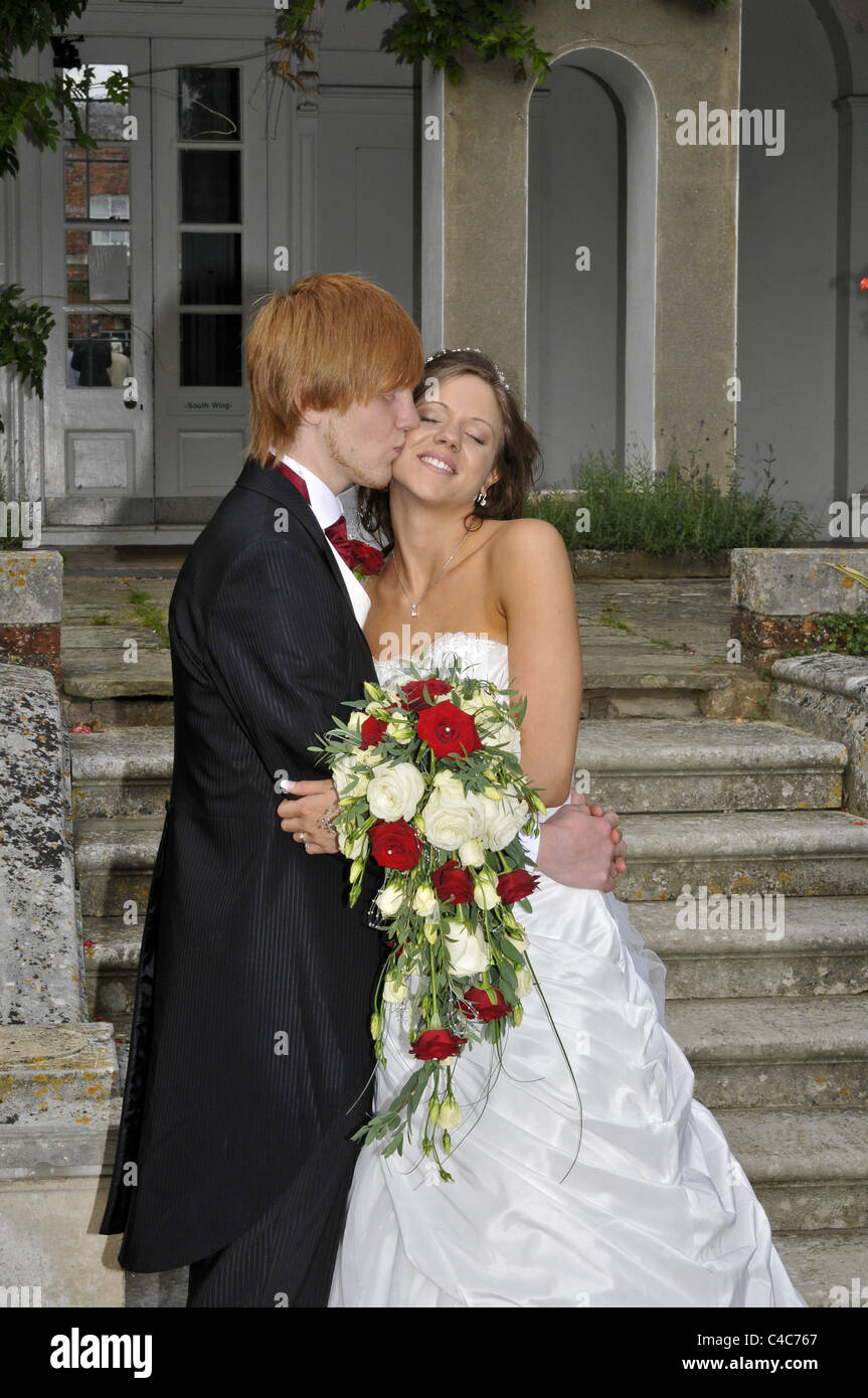 Young Bride And Groom Kissing After Wedding Ceremony With Colorful Bouquet