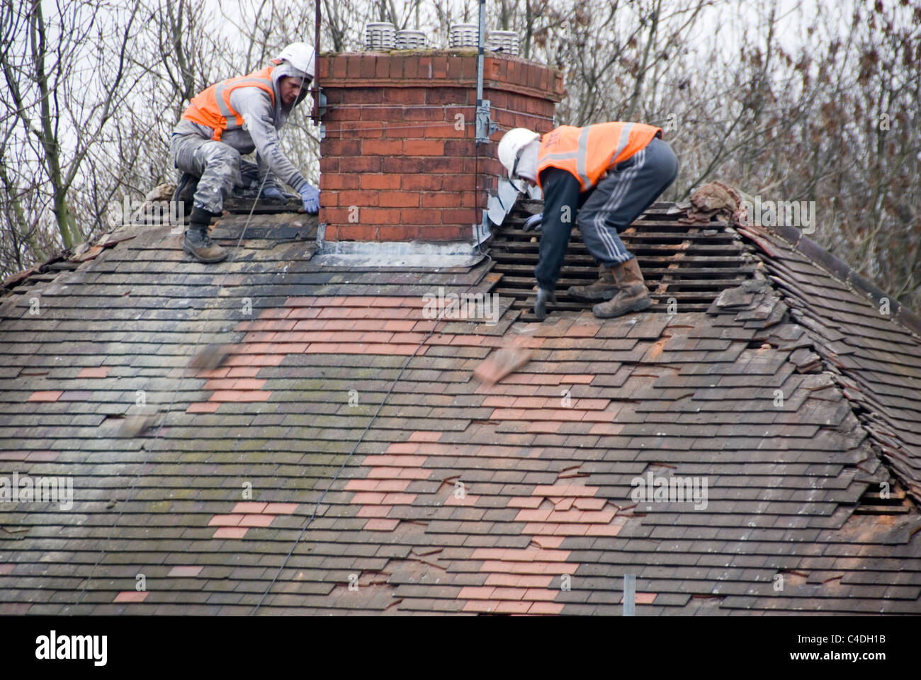 Stock Photo   Two Men Roof Of House Roof Stripping Off Old Tiles Re Roofing  ACIS Properties Hastilar Road South Sheffield March 2011