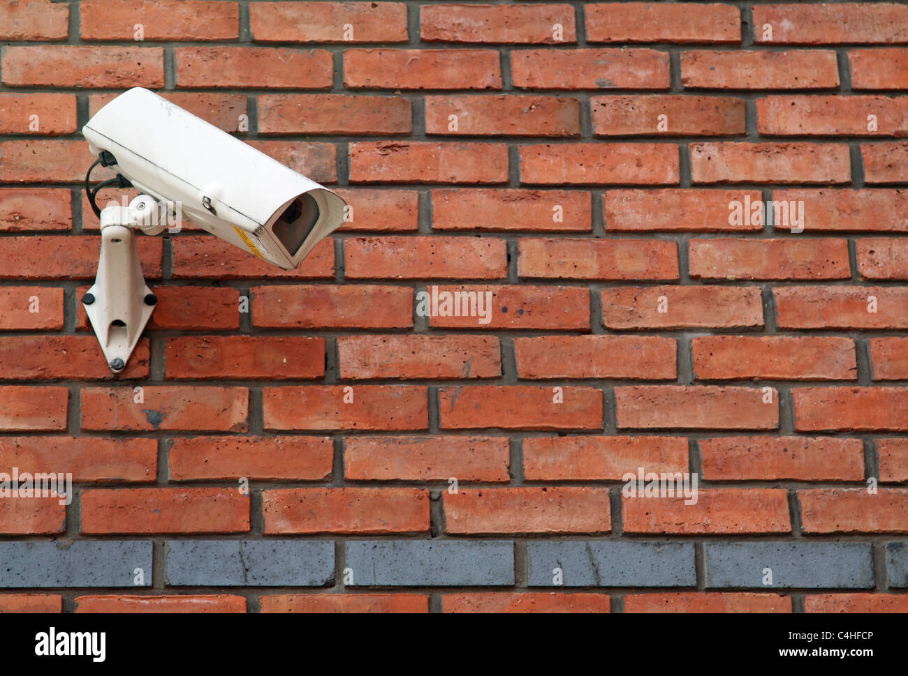 White Cctv Camera Mounted On A Red Brick Wall Stock Photo