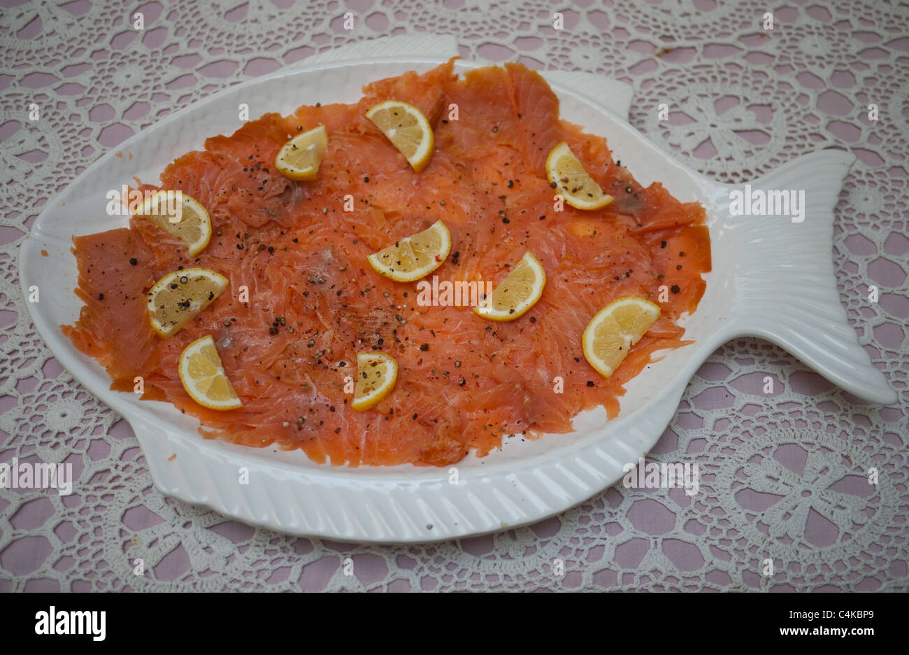 White Fish Shaped Platter Of Smoked Salmon With Lemon On Table With Table  Cloth