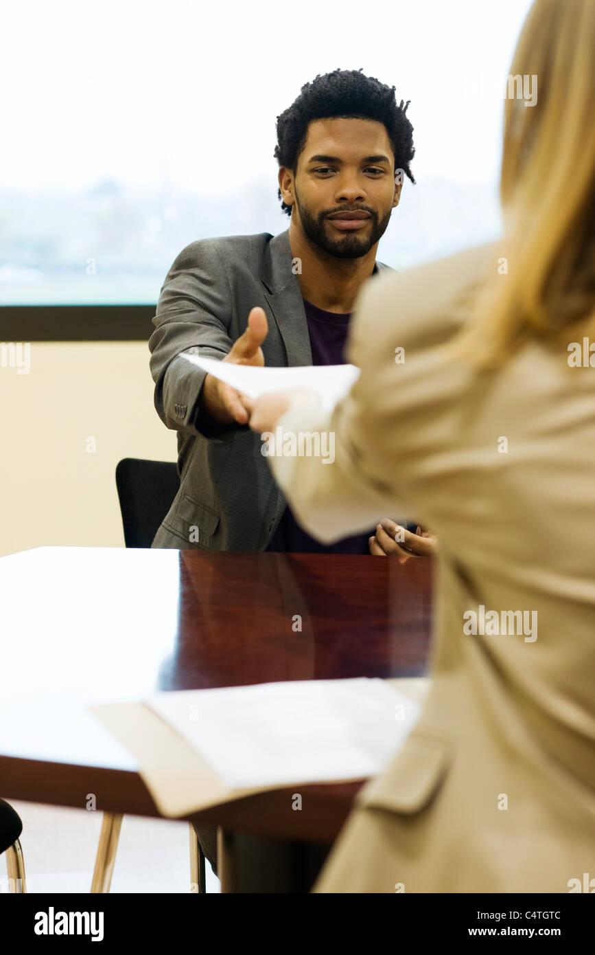 man handing prospective employer his resume during job interview