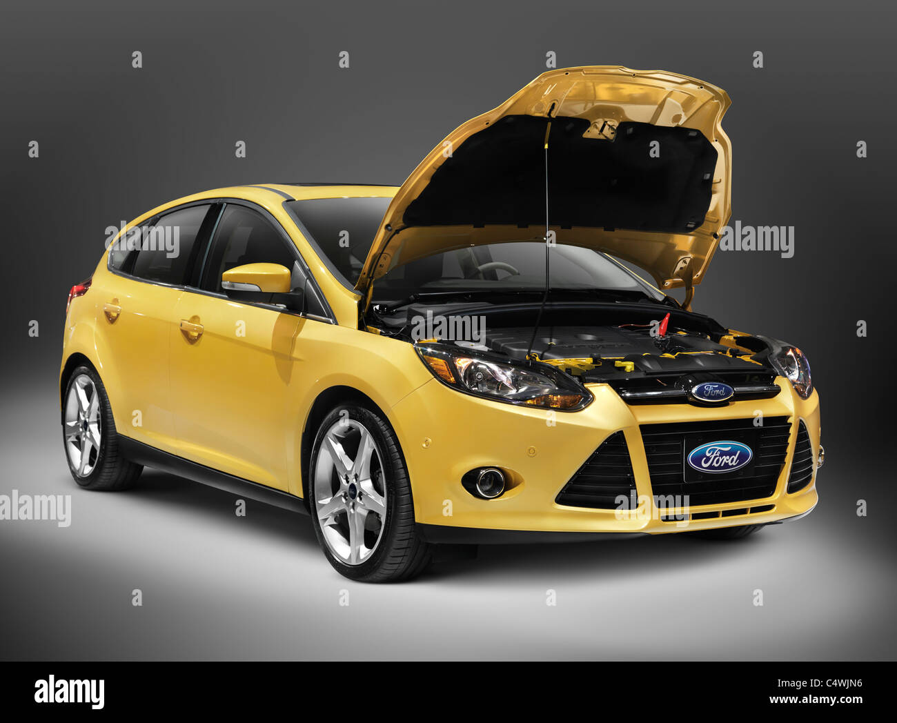 Yellow 2012 ford focus car with open hood isolated on white background with clipping path
