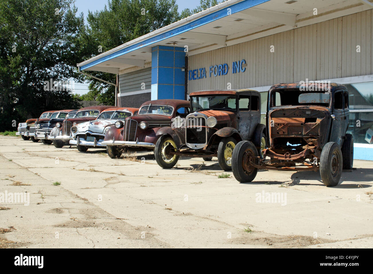 Vintage autos lined up outside a closed Ford dealership in Malta ...