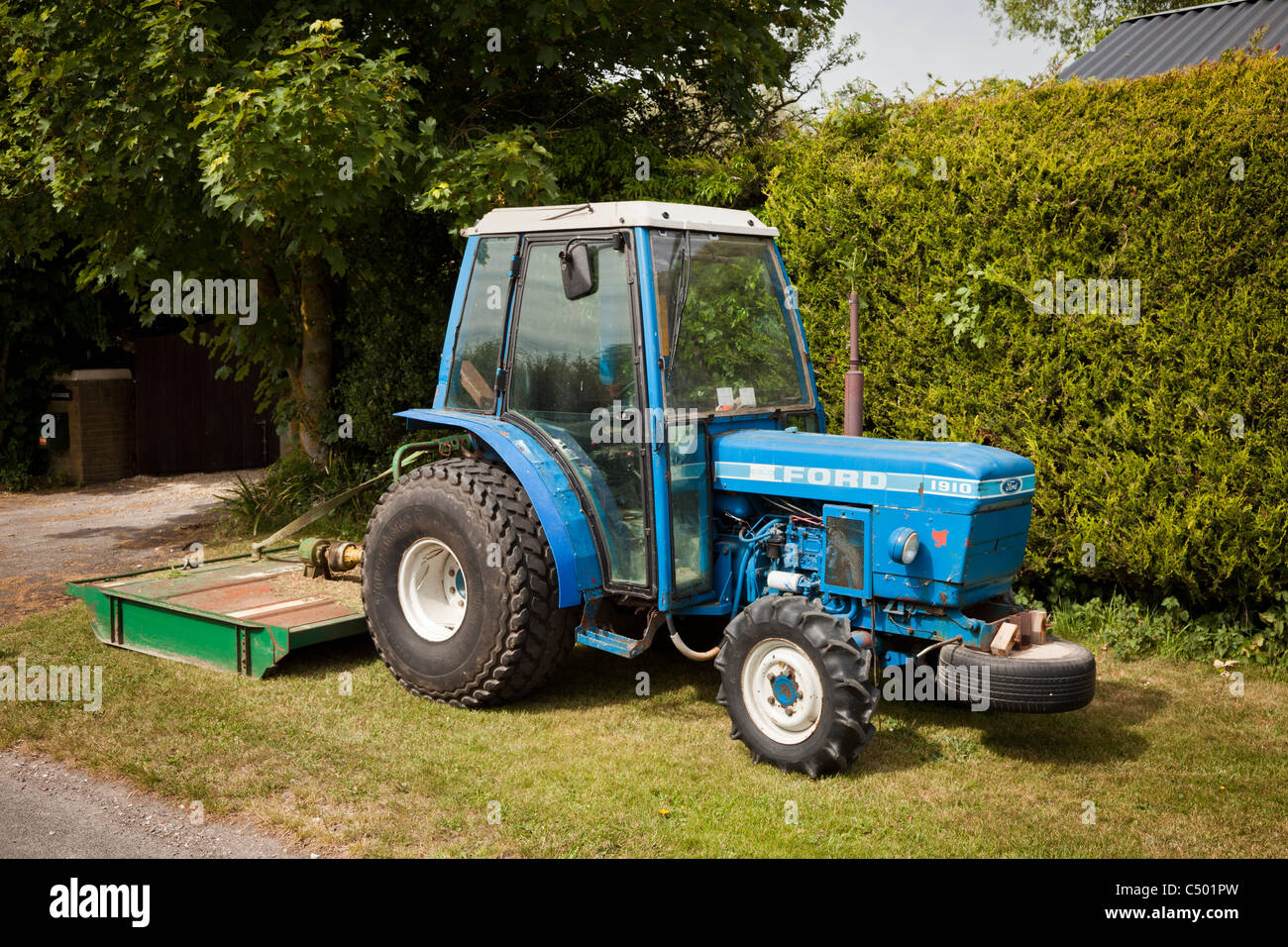 Ford 1910 compact tractor with grass cutting attachment stock image