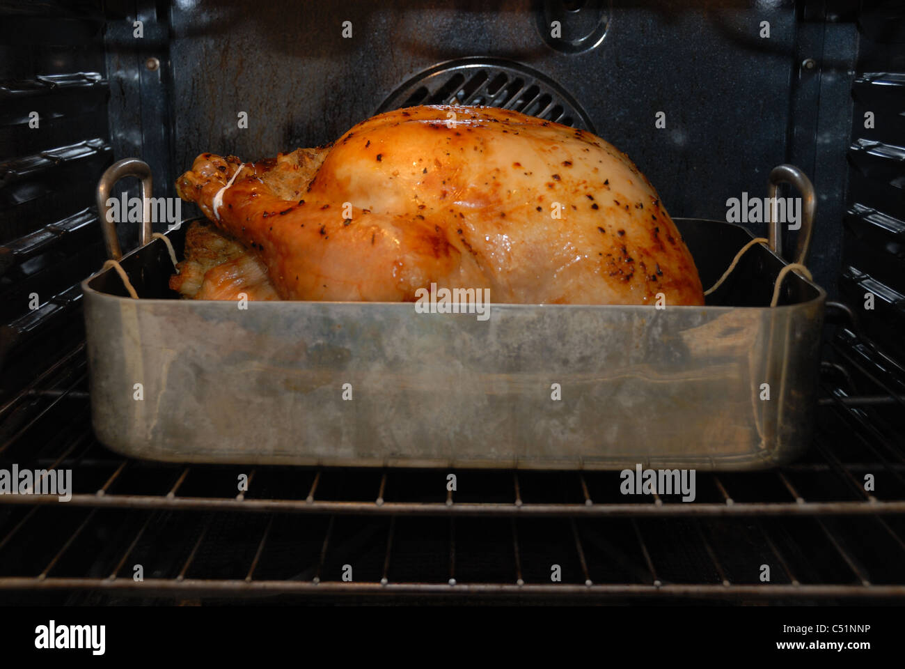 a turkey cooking in an open roasting pan inside an oven