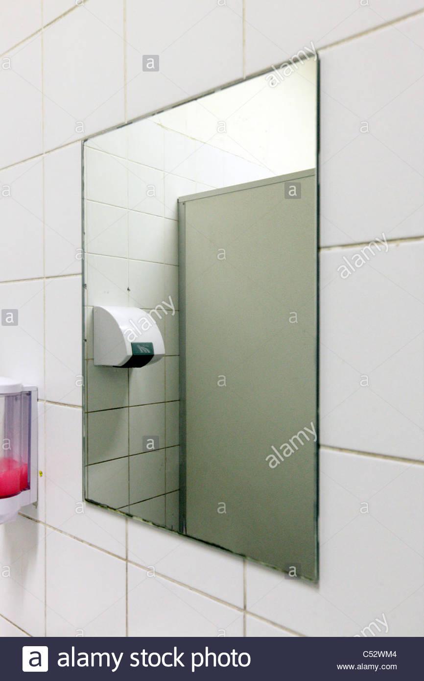 Public Bathroom Mirror mirror and soap dispenser in a public bathroom stock photo