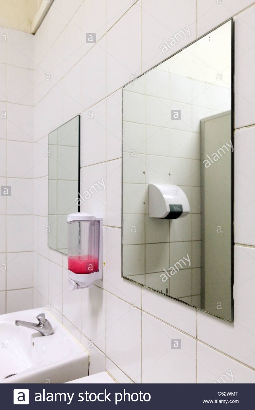 Public Bathroom Sink mirror sink and soap dispenser in a public bathroom stock photo