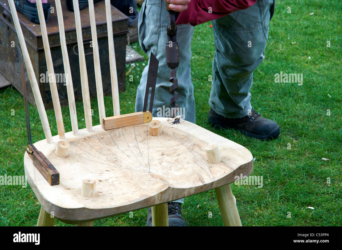 Bodger Or Traditional Furniture Maker Drilling A Hole In The Seat Of A  Rustic Chair During A Woodland Crafts Demonstration.