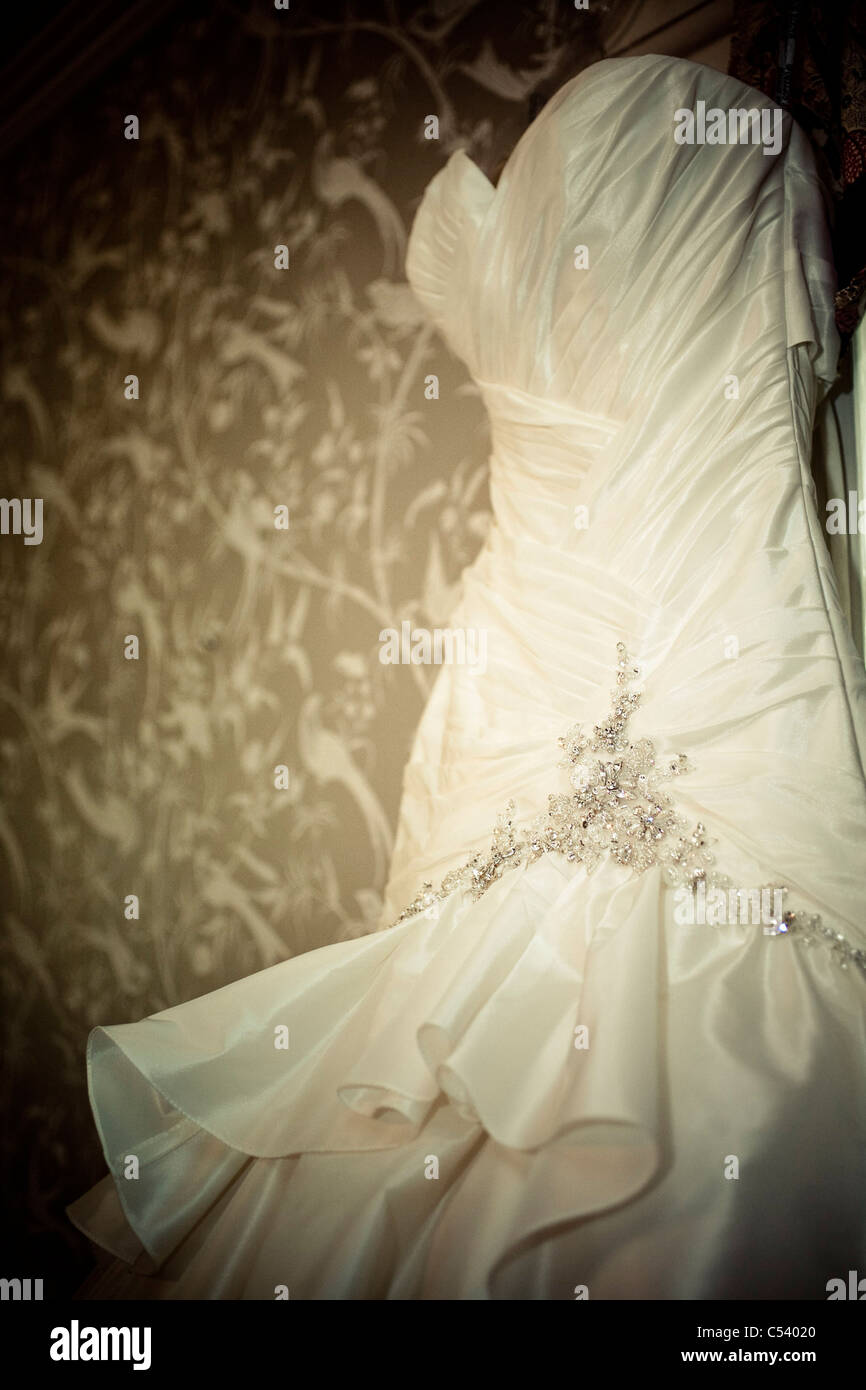 Wedding Dress Hanging On Wall With Patterned Wallpaper