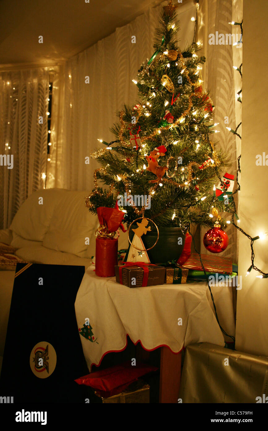 Small Christmas Tree On Table In Glowing Living Room With Lights  - Miniature Christmas Trees With Lights