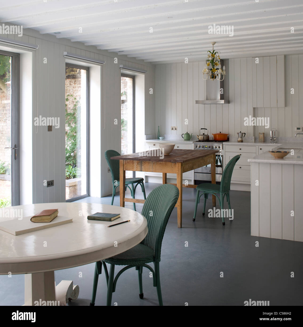 Kitchen Dining Room With White Painted Pedestal Table An Wood Panelled  Walls   Stock Photo