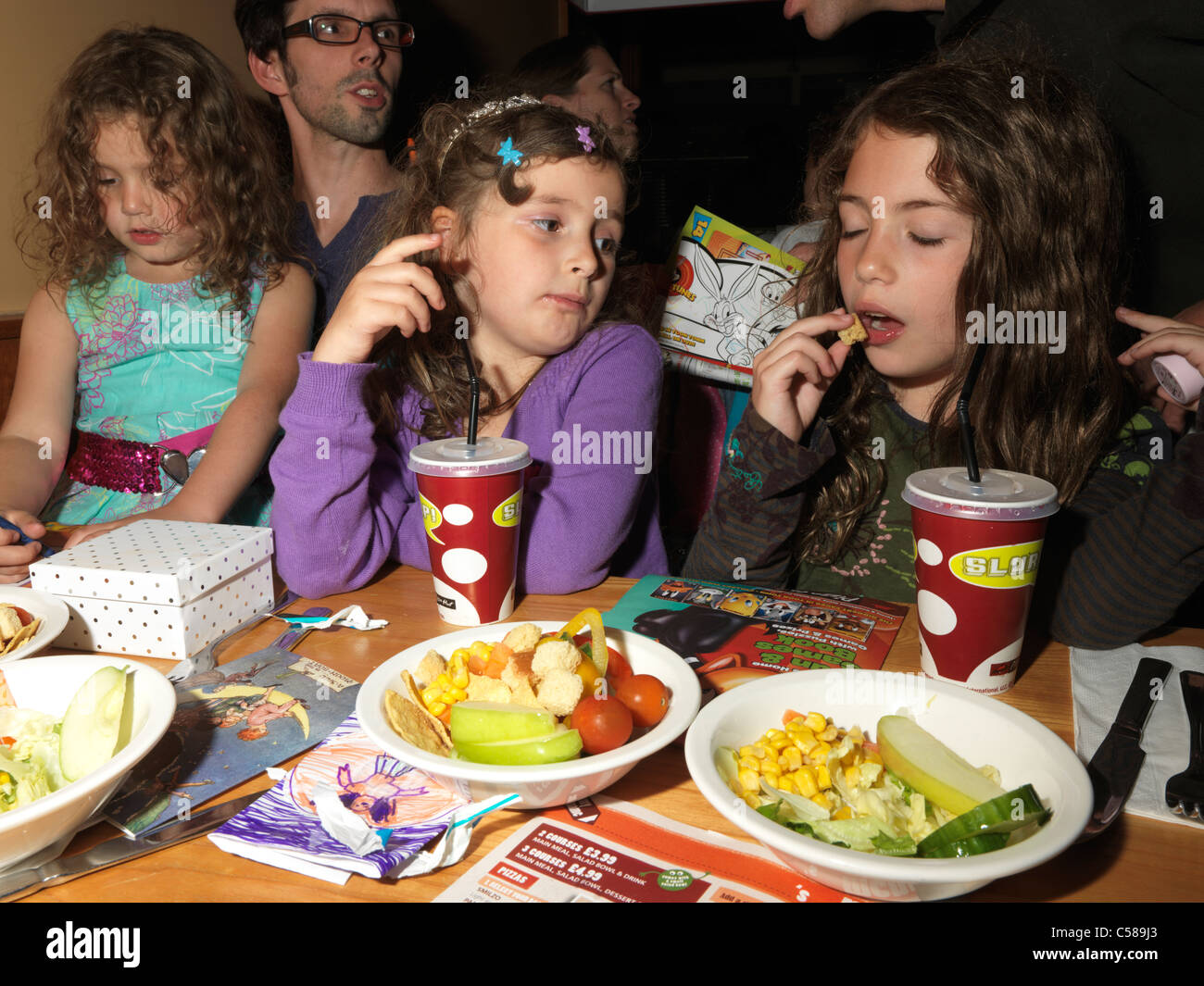 Childrens Birthday Party In Pizza Hut Young Girls Eating Stock - Childrens birthday parties pizza hut