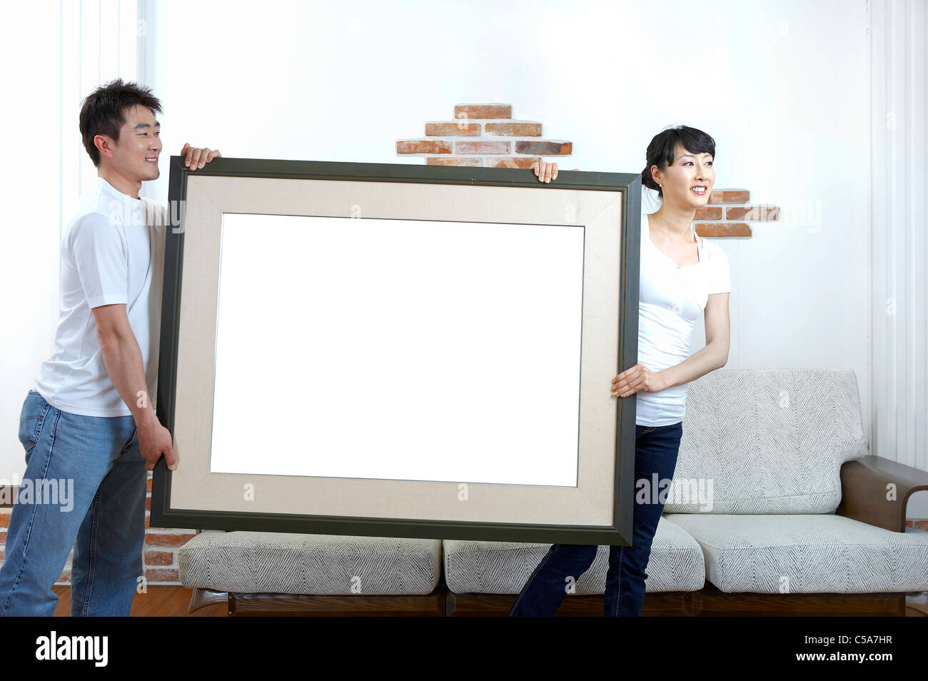 Side View Of Husband And Wife Holding Empty Picture Frame