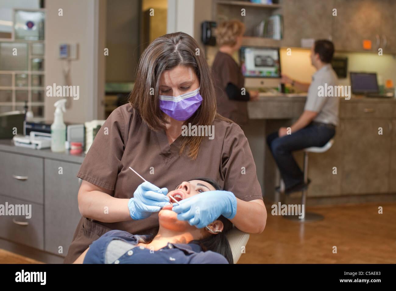 White female dental assistant reviews teeth of female Hispanic ...