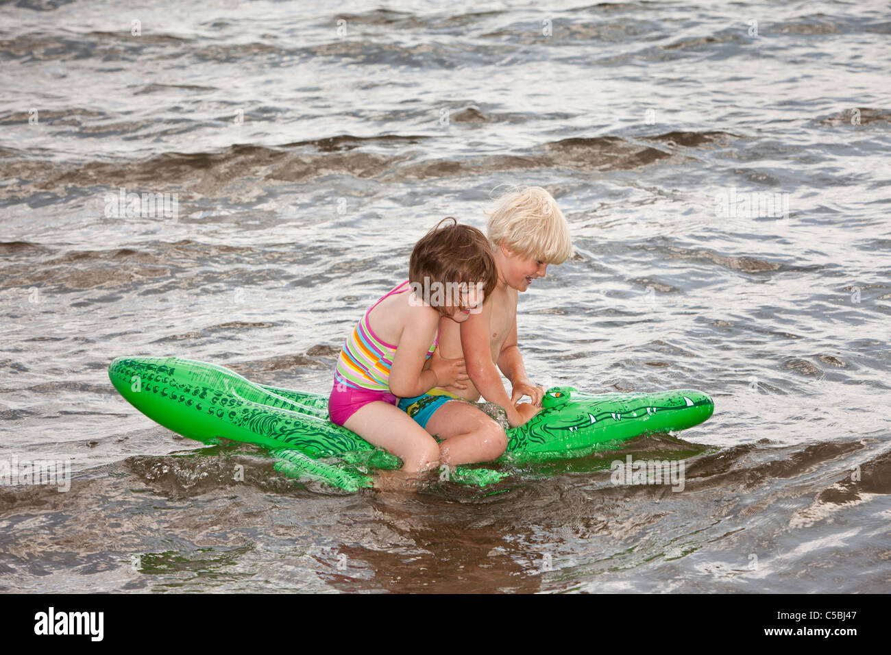 Side View Of A Boy And Girl Enjoying An Inflatable Crocodile Ride In Water