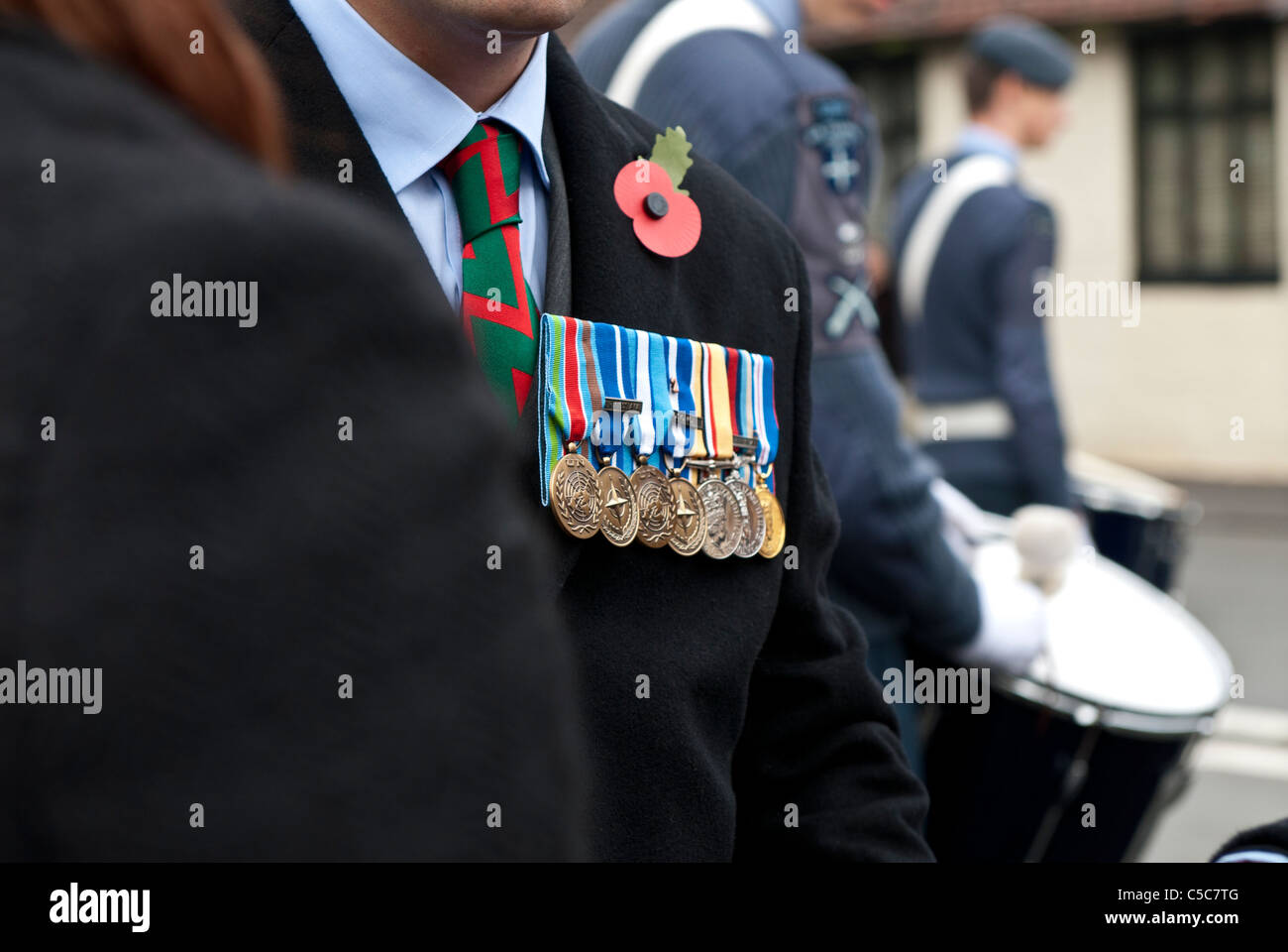 ex soldier wearing medals and a poppy at remembrance day parade