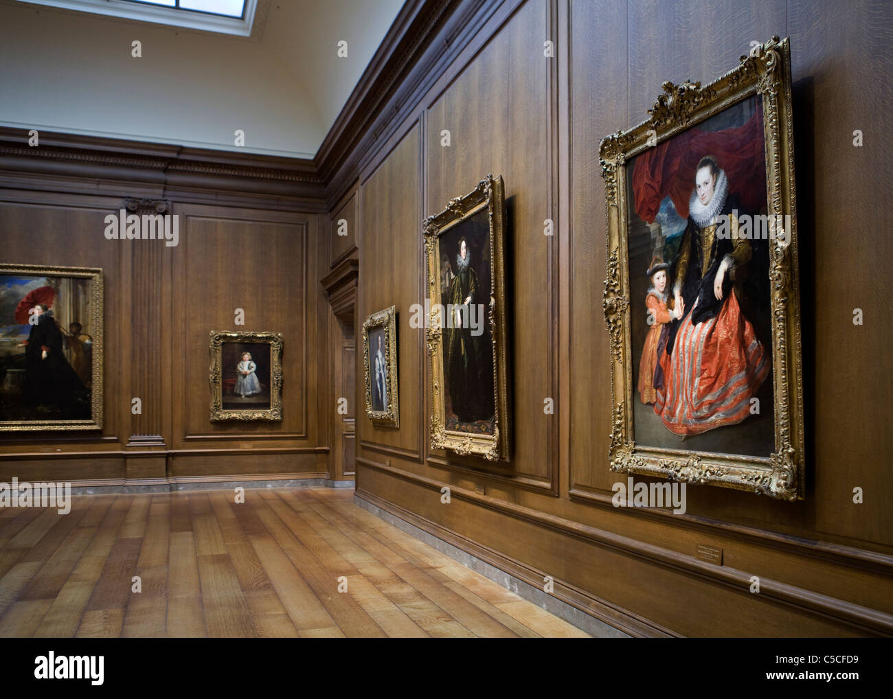 ... Fine-art paintings hang on an art gallery walls lined in fine woodwork  - Stock