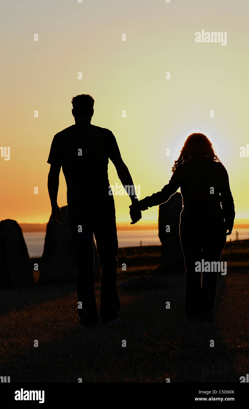rear view of a silhouette couple holding hands and walking on the beach at sunset
