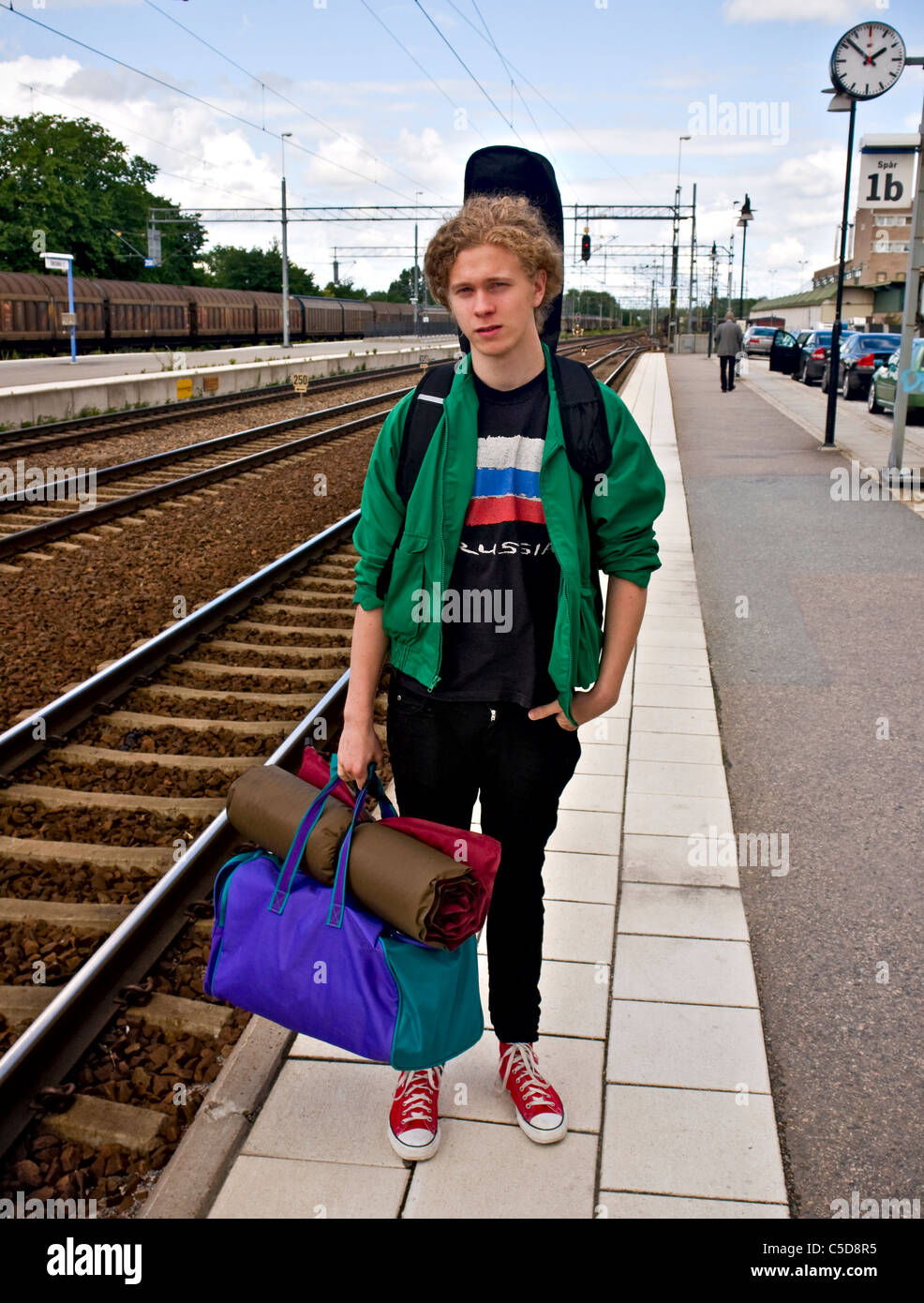 Portrait Of A Young Man With Bag Carrying Guitar Behind His Back At The Railway Station Platform