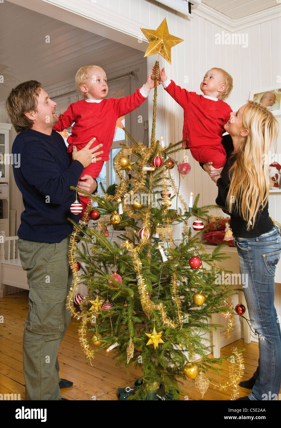 Kids Decorating For Christmas couple with two kids decorating the christmas tree at home stock