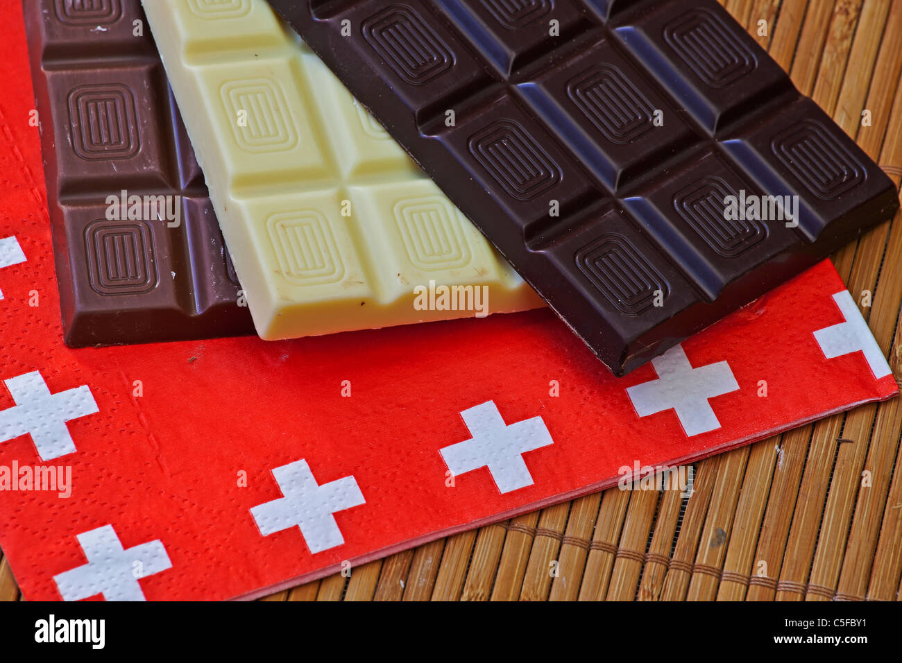 three panels swiss chocolate on a place mat with a napkin with ...