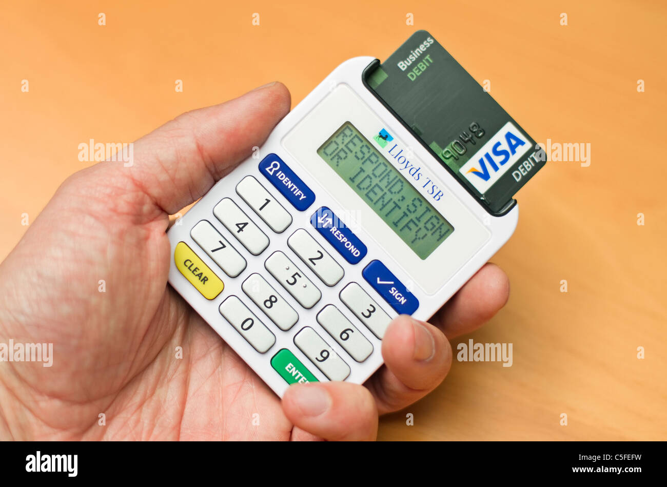 Lloyds tsb bank credit card issued in the uk stock photo royalty picture by james boardman male adult hand using a lloyds tsb bank card reader to access his online banking facilities magicingreecefo Image collections