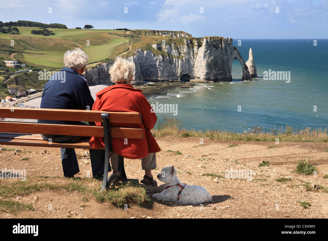 senior-couple-with-dog-sitting-on-bench-