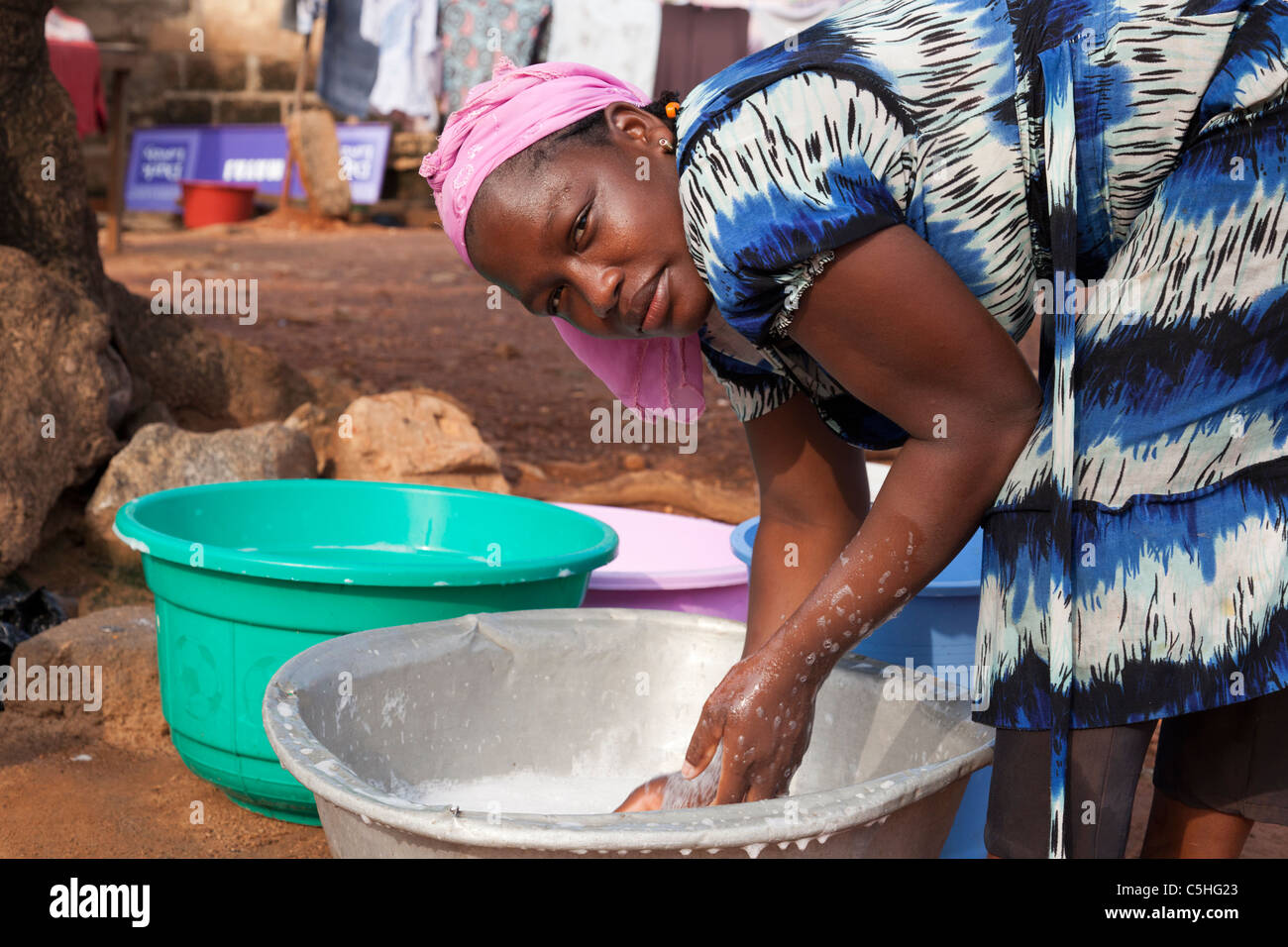 Portrait of an African woman washing clothes by hand in ...