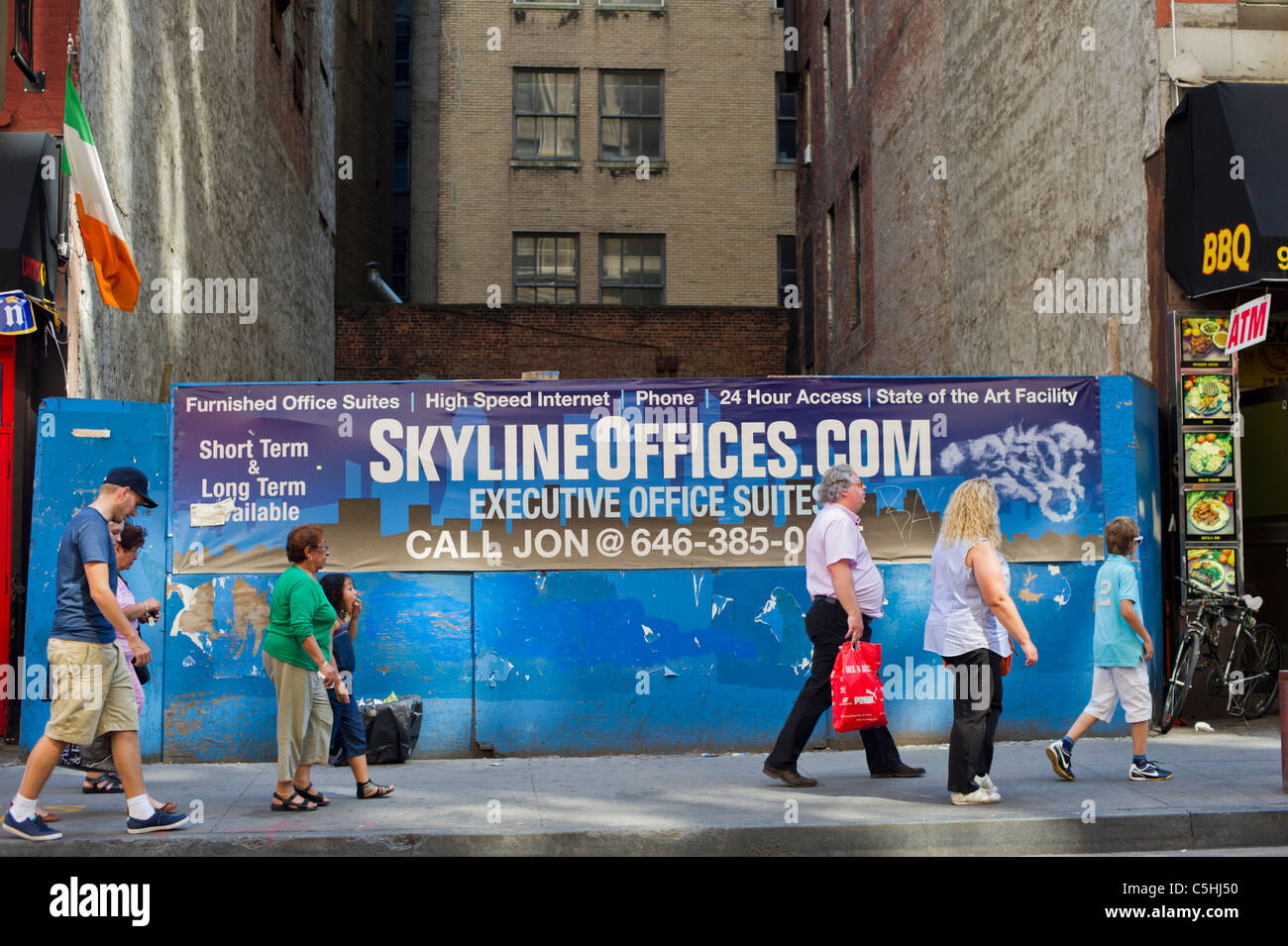 pedestrians pass a banner advertising office space for rent in lower manhattan in new york advertising office space