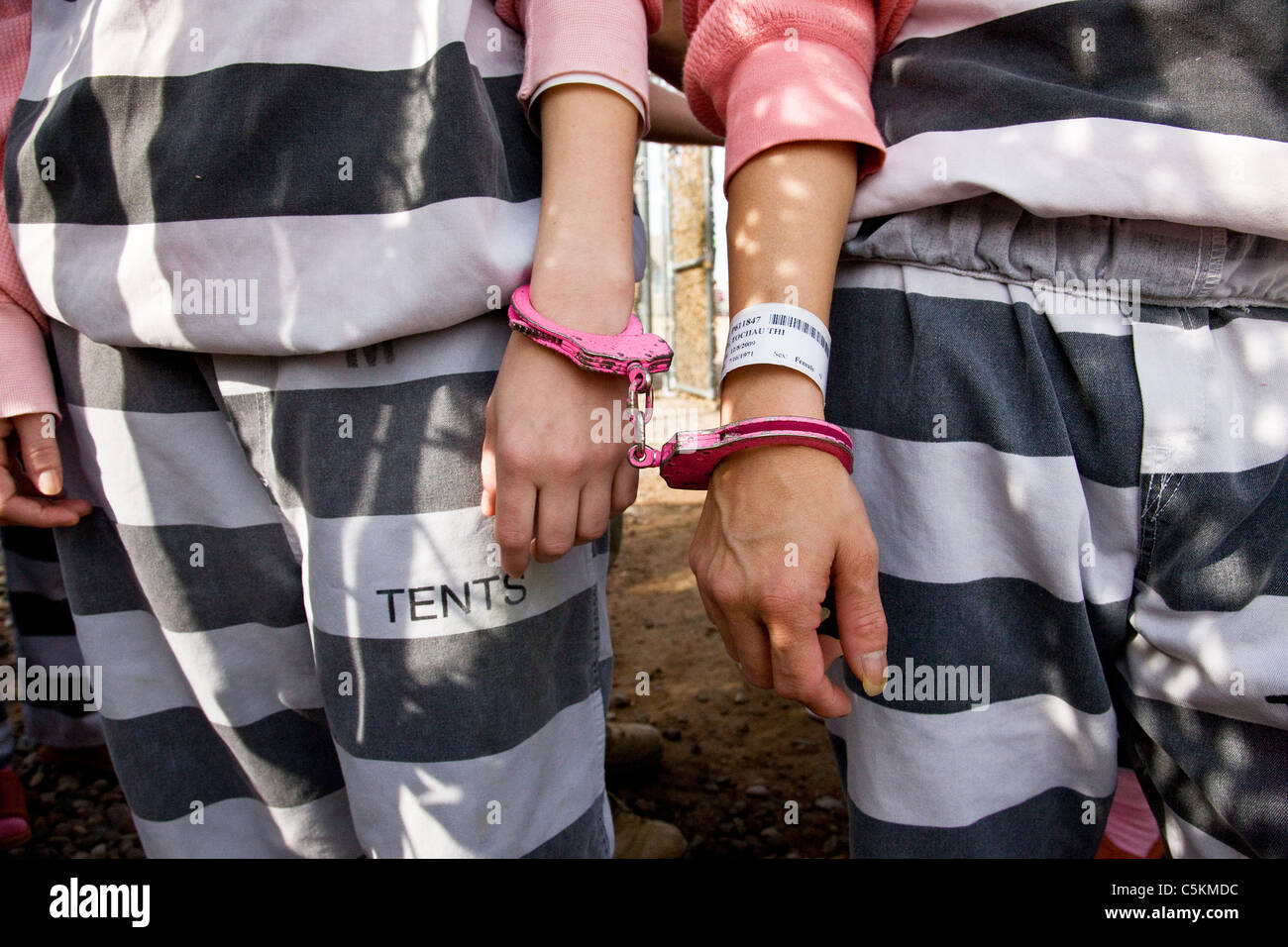 Two female inmates are handcuffed together with pink handcuffs at Estrella Jail in Phoenix Arizona & Two female inmates are handcuffed together with pink handcuffs at ...