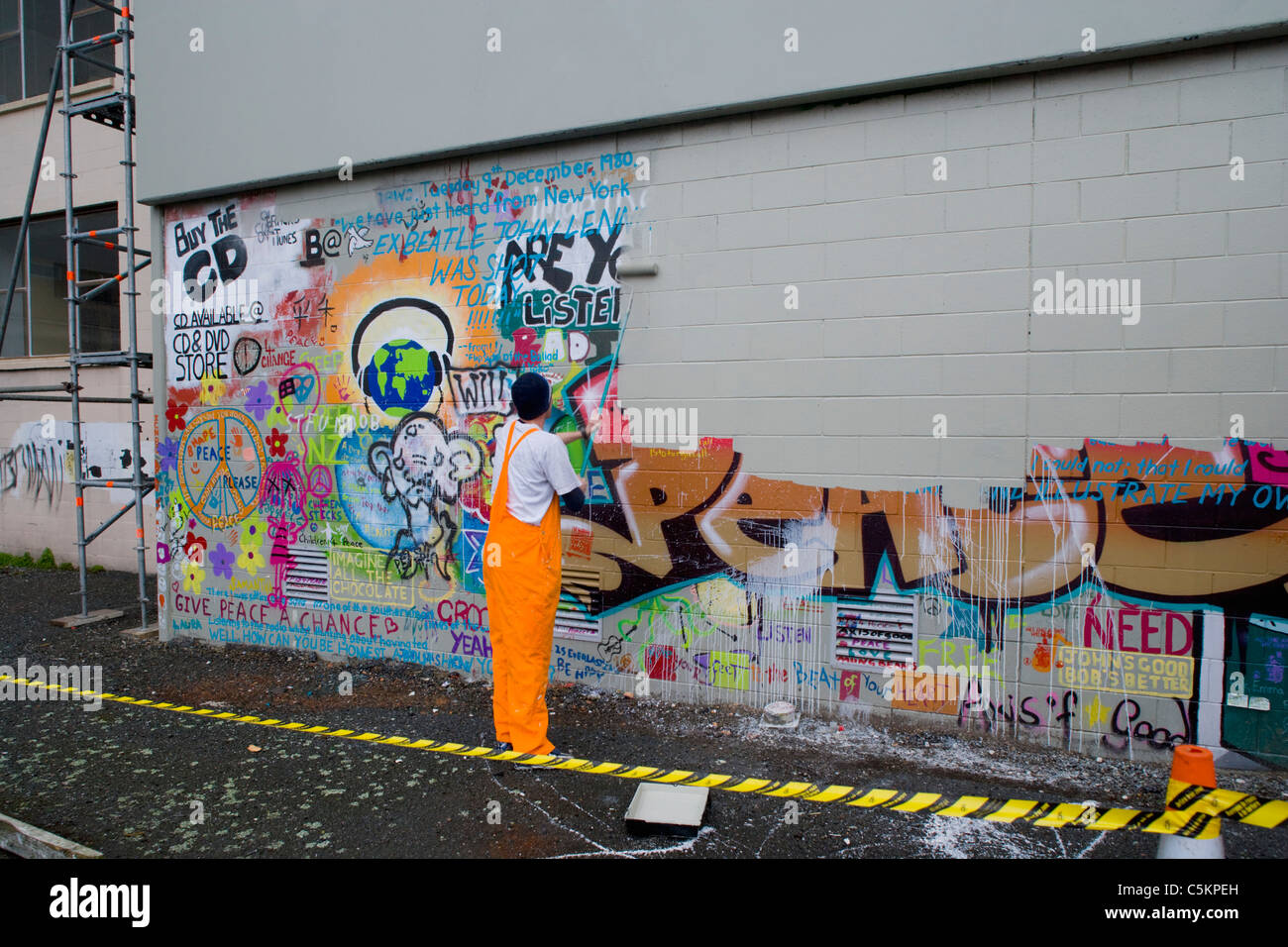 Graffiti wall painting - Man Painting Over Graffiti On A Wall With A Paint Roller
